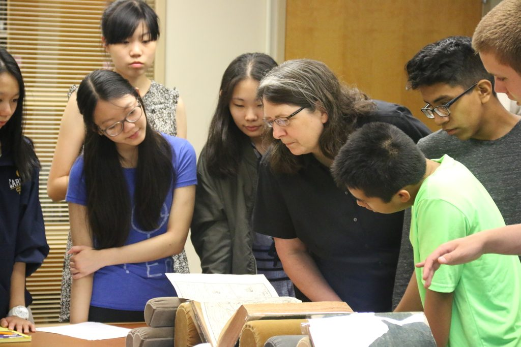 Humanities students looking at maps