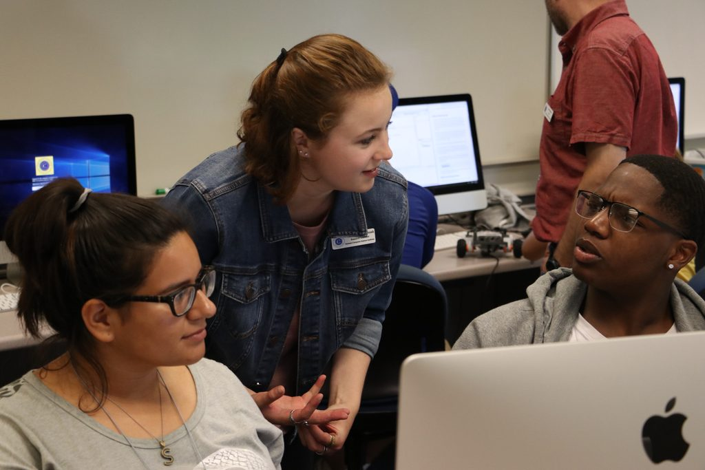 A computer science research assistant helping students in lab
