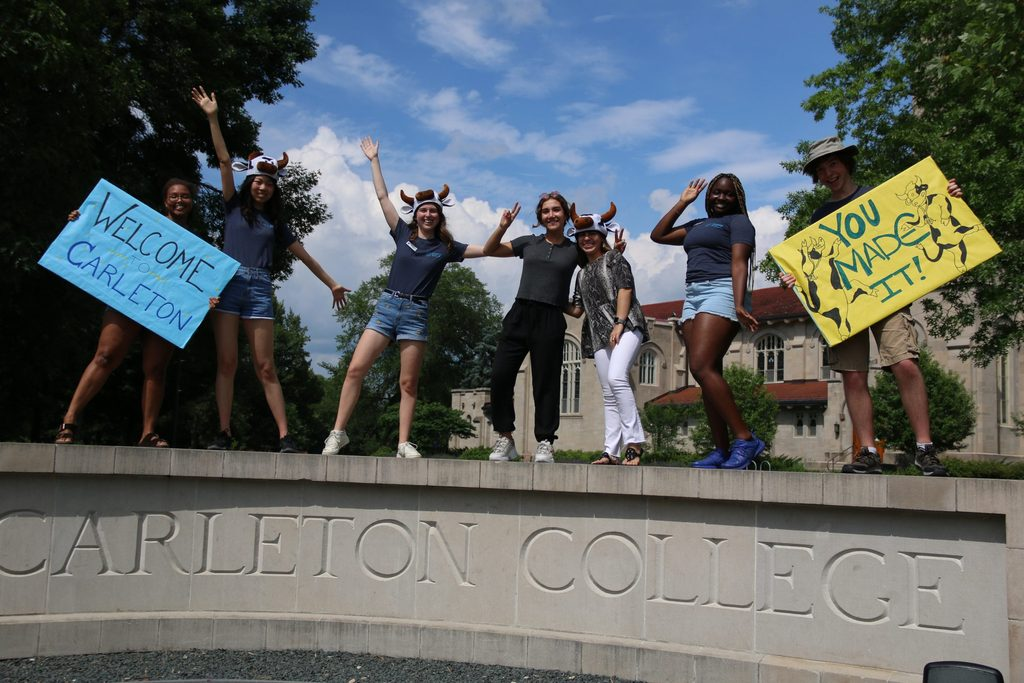 Students holding welcome signs on top of the Carleton College sign