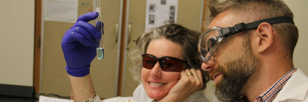 APSI science participants examining solution in a test tube with goggles on