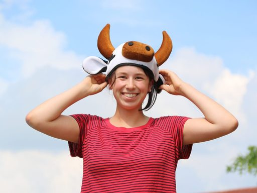 Student holding a cow hat on their head and smiling