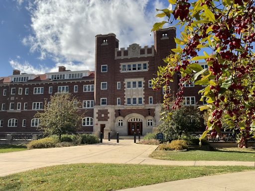 The entrance to Burton Hall, a red brick building, sprawls the background to this photo with some tree branches covered in pink berries coming into the right foreground.