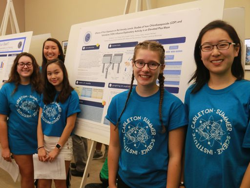 Five science students posing by their poster at the science poster session. All are wearing their blue science institute t-shirts