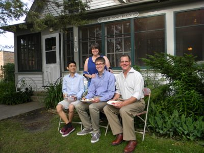 Four people pose for a photo in front of a house