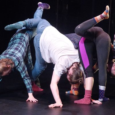 Dancers upside-down with one leg up huddled together