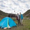 two students stand besde a tent