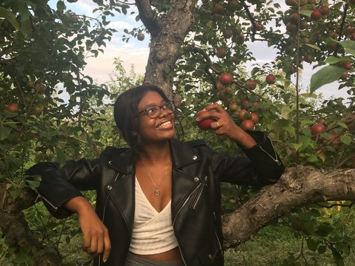 Bethstyline Chery stands beneath an apple tree