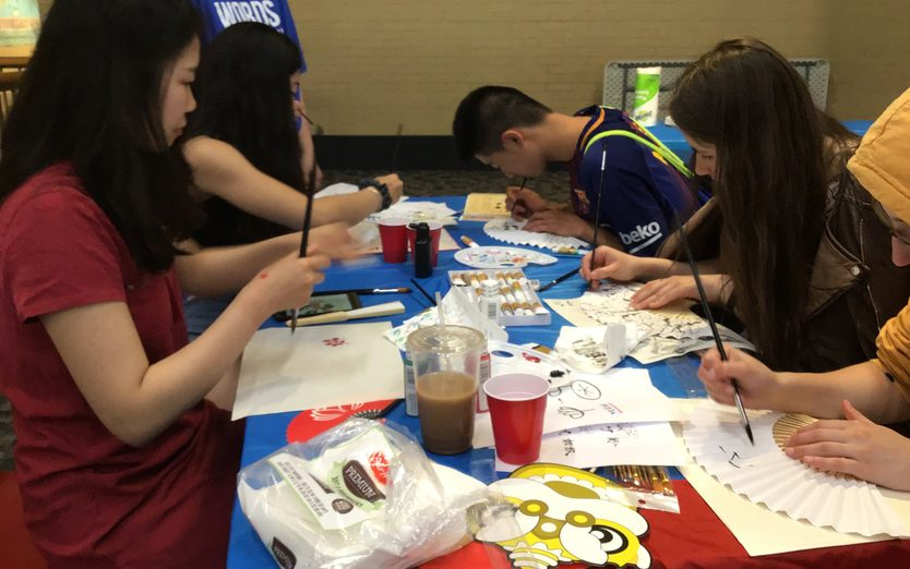 a group of students painting at a table
