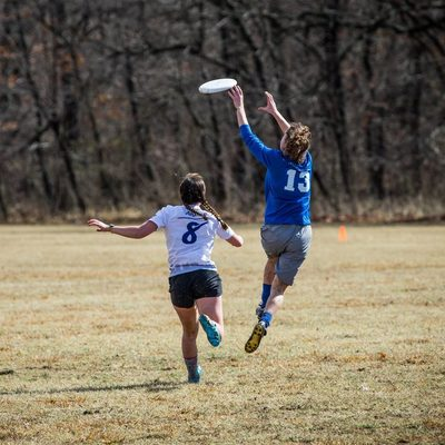 a player jumps in the air to catch a Frisbee
