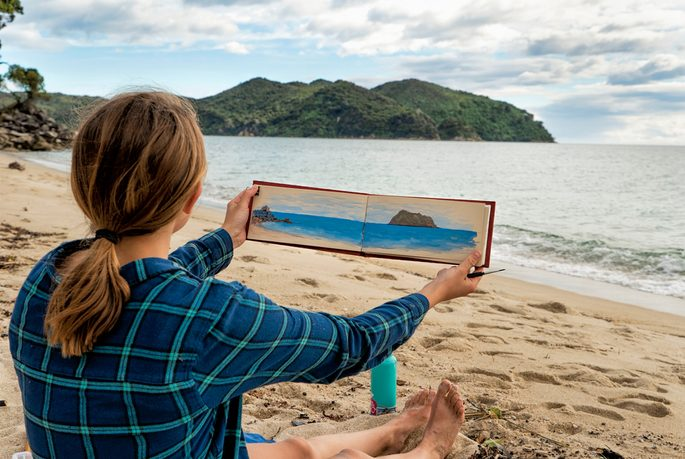 A woman holds a painting while sitting on a beach