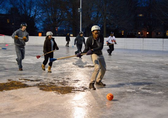 students play broomball at night.