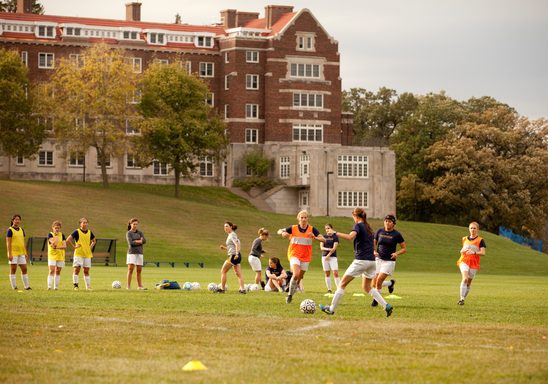 students play soccer with Evans Hall in the background