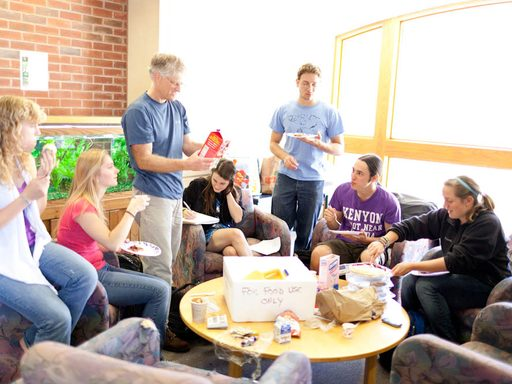 Students and professor sharing snacks around a circular table