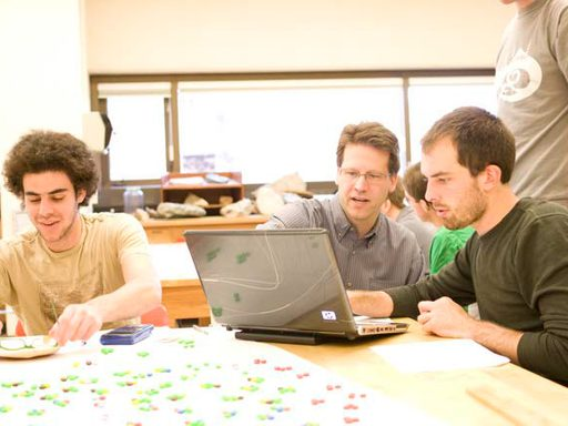 Students and professor looking at a laptop