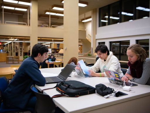 Three students with computers studying together