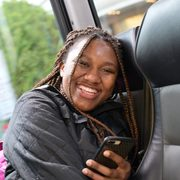 A student on a bus holding a mobile phone