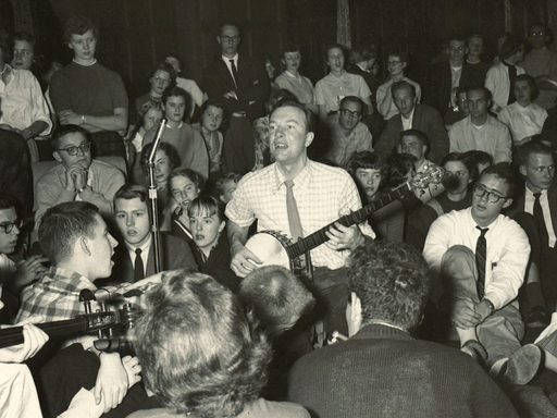 Pete Seeger plays a banjo amidst a crowd of students