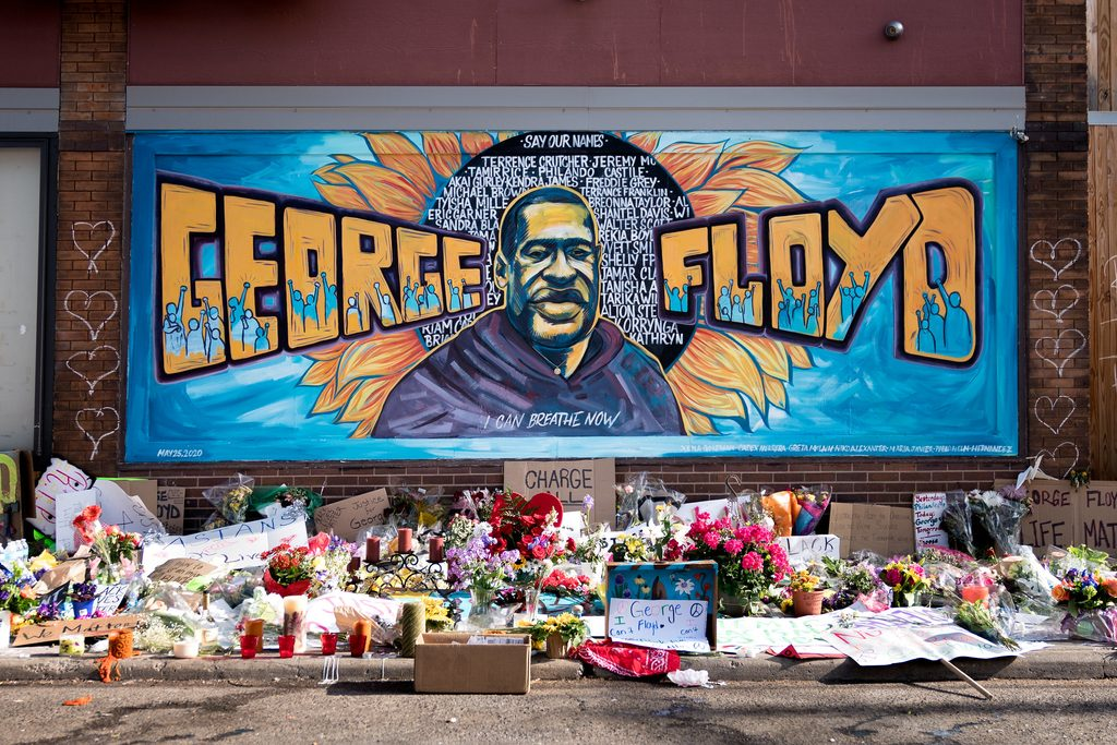 A mural of George Floyd with flowers placed underneath.