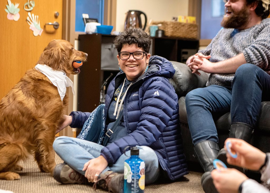A student smiles with a dog