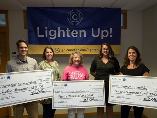 Staff present proceeds from the annual Lighten Up! sale to representatives of local non-profits.