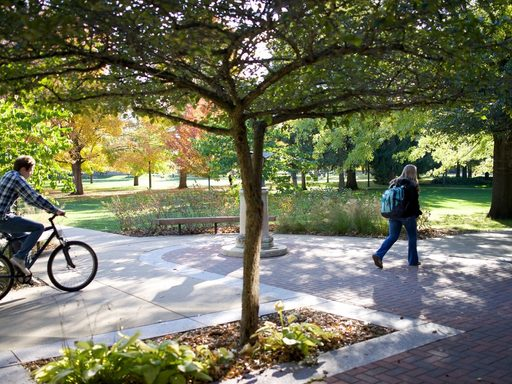 Students walk and bike through campus in autumn.