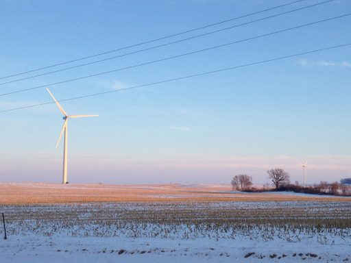 A windmill in a winter field.