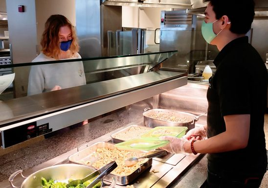 A Bon Appetit staff member dishes up a meal for a student