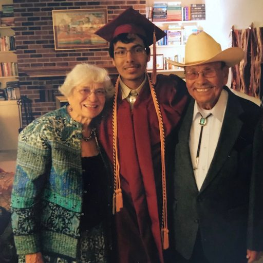A student in graduation garb with his grandparents