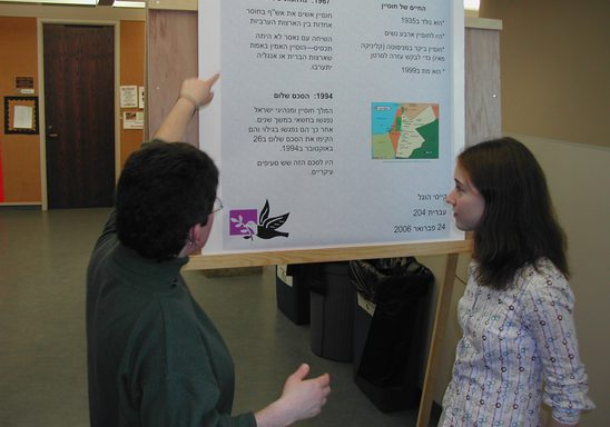 a professor and a student looking at a research poster