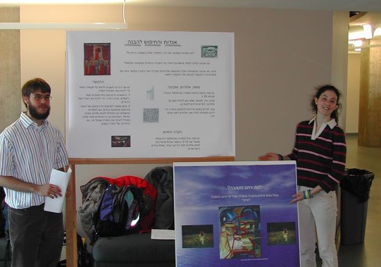 two students standing beside academic posters