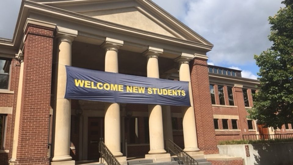 """Image of the front of Sayles Hill Campus Center with a """"Welcome New Students"""" banner."""