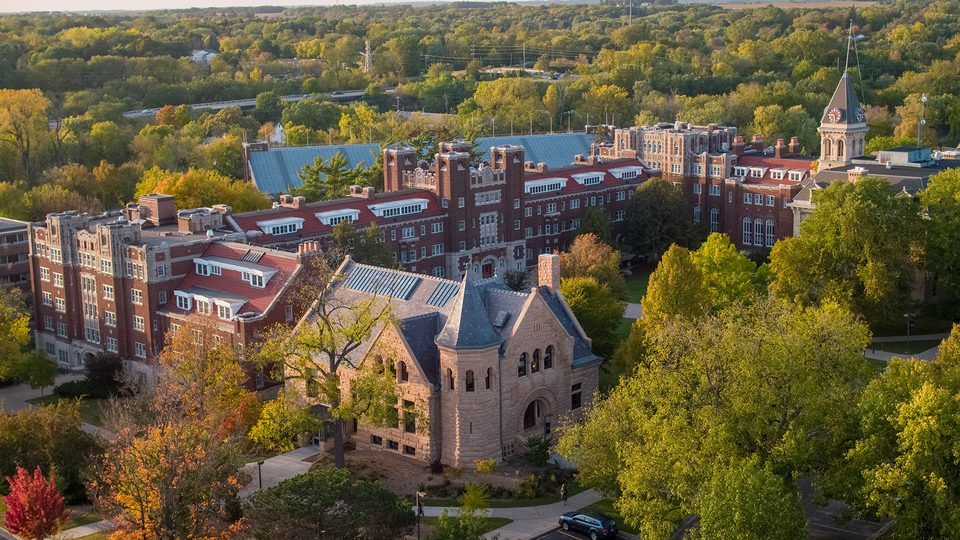 Aerial view of a college campus featuring buildings and treetops