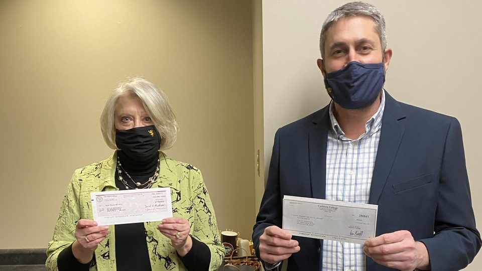 Carleton Vice President and Treasurer Eric Runestad and St. Olaf Vice President and Chief Financial Officer Janet Hanson present the colleges' annual donation to the City of Northfield