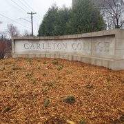 flowers in front of Carleton sign by townhomes