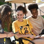 students smile on a golf cart