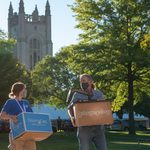 A student and adult with moving boxes with the chapel in the background.