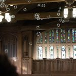 bubbles float with the stained glass chapel windows in the background