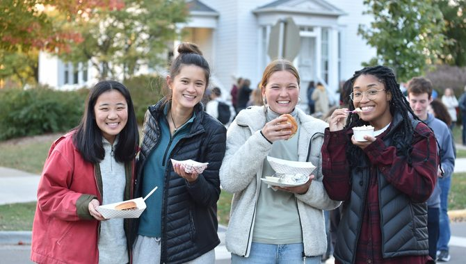 four female students eating food at the street fair.