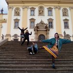4 students pose informally in front of ornate building