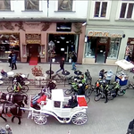 A busy street with a horse-drawn carriage and bicyclists