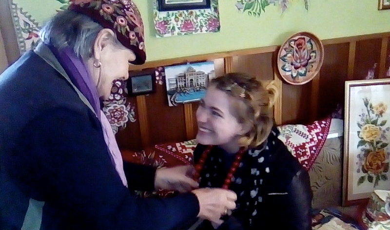 An older woman places a necklace on a student