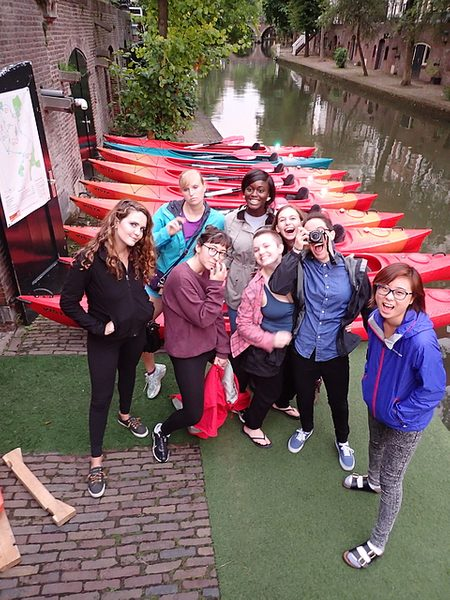 Group smiles in front of a canal