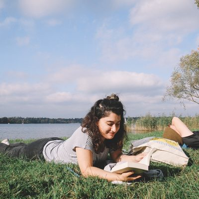 Student lying down reading nearby a river