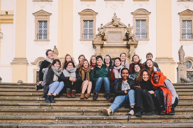 Students and faculty sitting together on the stair and posing for a photo