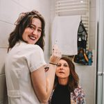 Student applying makeup to professor's face in the bathroom