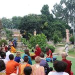 Students listen to a monk speaking outside