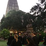 Students meditate outdoors in front of the temple
