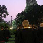 Meditators sit outside of the temple