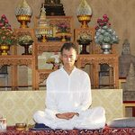 A man sits cross-legged and meditates in front of an ornate altar