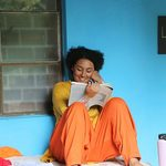 A woman smiles as she reads a book